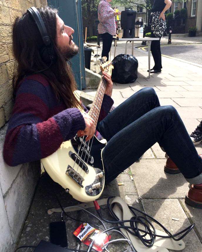Bass player Nick Fyffe preparing in the sun outside St. Mary's church. Photo: Sunflower Jam