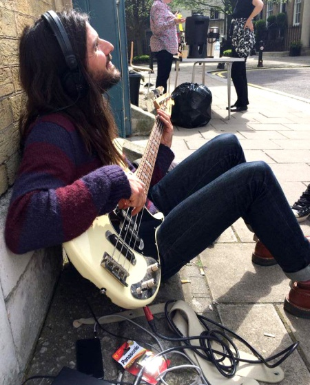 Bass player Nick Fyffe preparing in the sun outside St. Mary's church. Photo: Sunflower Jam